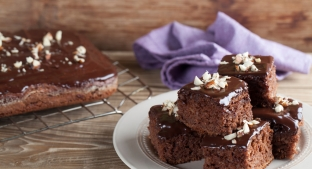 stack of chocolate Brownies on  white plate on a wooden table